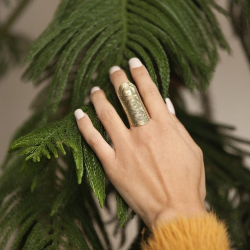 Long, boho floral etched brass ring by Baizaar Jewelry on the hand of a female model.