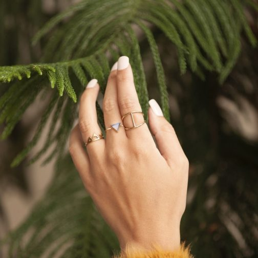 Nickel-free brass trinity stone ring on a woman's hand with green foliage backdrop.