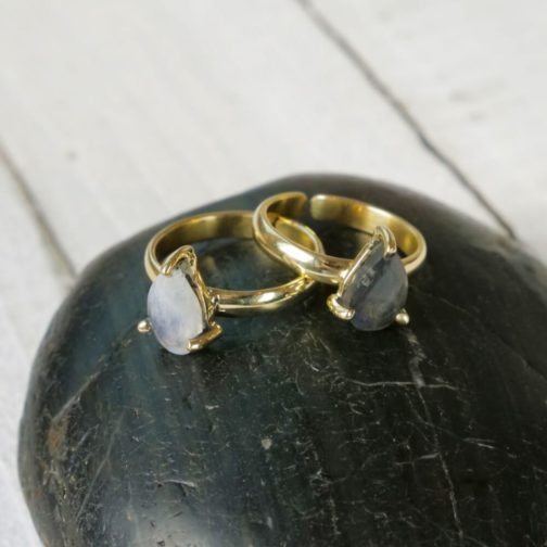 Two brass tear drop prong rings with faceted moonstone and labradorite stone, sitting on a black polished stone.