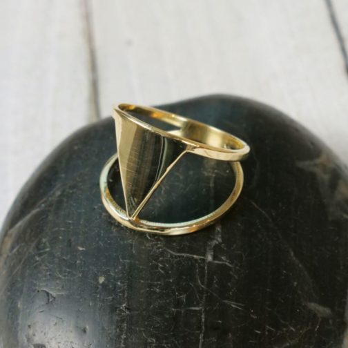 Close up photograph of brass cut out triangle ring.