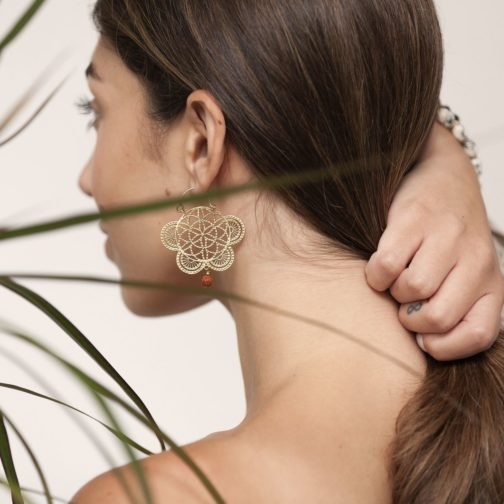 Flower of life design earrings featuring a Rudraksha seed dangle worn by a female model holding her long brown hair.