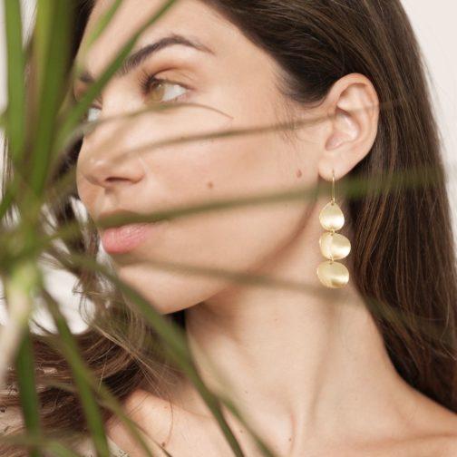 Brushed brass triple pod earring worn by a brunette female model.