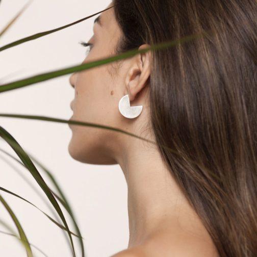 Woman wearing handmade silver Pac Man earrings from Baizaar Jewelry.
