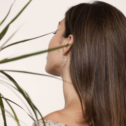 Woman looking away from camera wearing silver stacked triangle earrings.