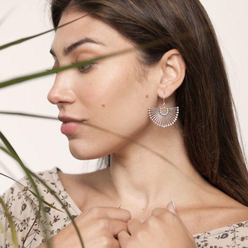 Female model wearing sterling silver peacock earrings from Baizaar Jewelry.o