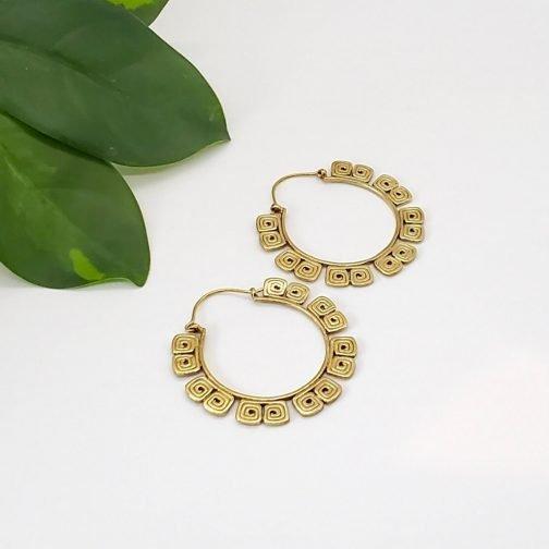 Brass labyrinth hoop earring.